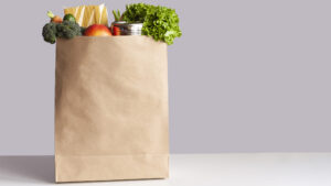 Various grocery items, including fruits and vegetables, in a paper bag on a white table opposite gray wall.