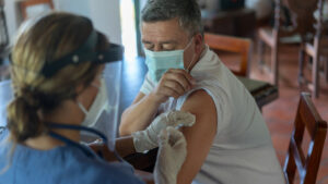 Adult Latin American man getting a COVID-19 vaccine at his rural house.